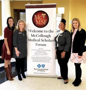 Health professions advisors standing around the McCollough Medical Scholars Forum sign