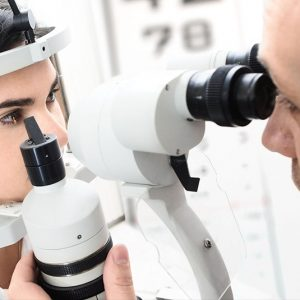 optometrist examining a patient's eyes